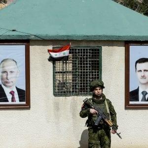 صورة تم التقاطها في 1 آذار/مارس من عام 2018 لأحد أفراد الشرطة العسكرية الروسية يقف حارساً بين صورة الرئيس السوري بشار الأسد (إلى اليمين) والرئيس الروسي فلاديمير بوتين (إلى اليسار) خارج نقطة حراسة عند حاجزعلى ضواحي دمشق - ا(لؤي بشارة/وكالة الصحافة الفرنسية /غيتي إيماجز)